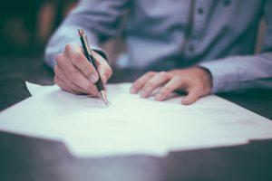 Homme signant plusieurs documents