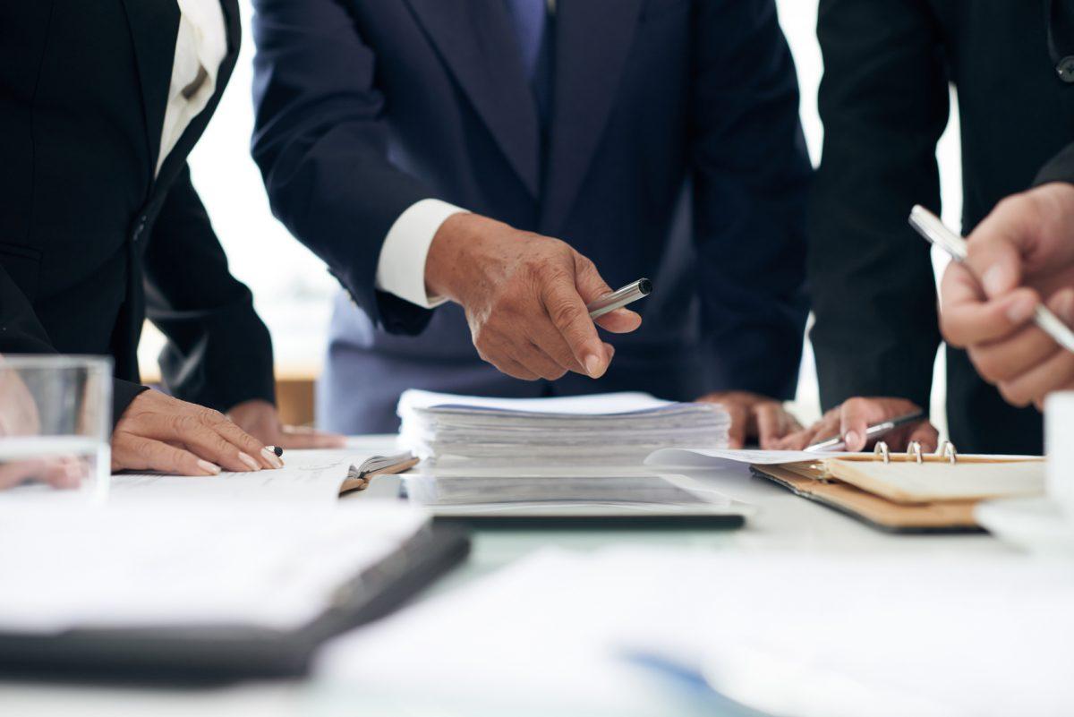 Homme pointant du doigt une pile de documents